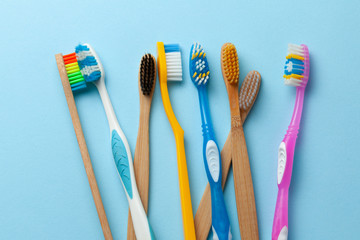 Colored toothbrushes on blue background.