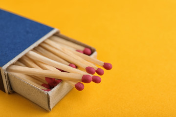 Cardboard box with matches on color background, closeup. Space for text