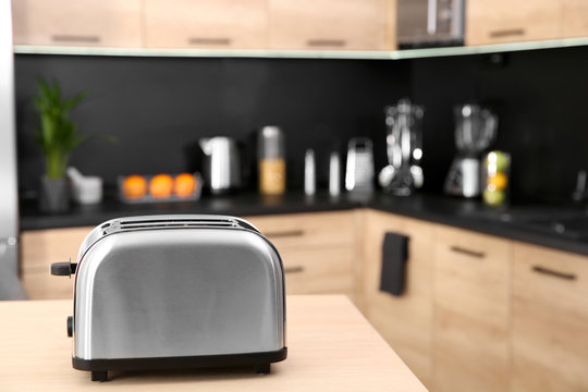 Modern toaster on table in kitchen, selective focus