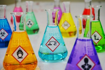 Many of Erlenmeyer flask with colorful solution and Variety type of chemical hazard warning symbols labels. Focus on Corrosive sign,symbol.