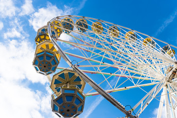 Ferris wheel with colorful gondolas in a funfair, against a beautiful blue sky with white clouds.