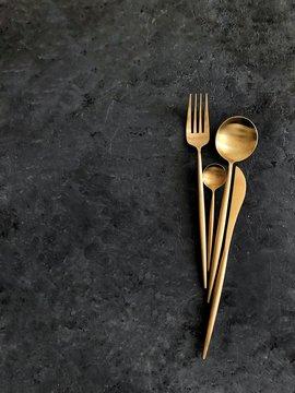 Golden cutlery on dark background