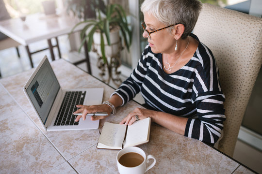 Mature beautiful woman working on her laptop at home. Elderly woman typing on her laptop while reading notes from her notebook outside on the balcony