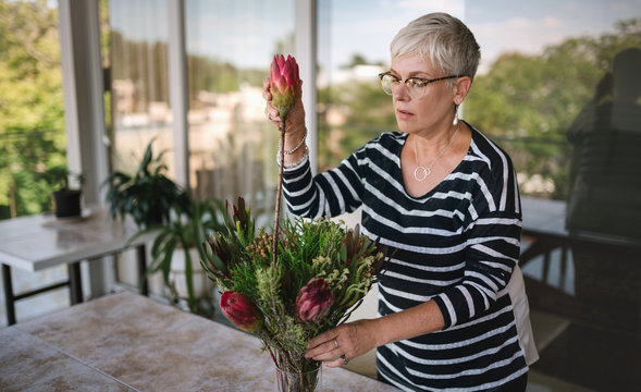 Portrait of a senior woman adding a protea flower to a bouquet. Elderly woman enjoying arranging flowers as a hobby