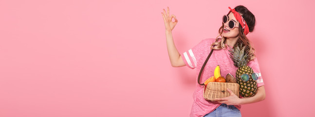 Beautiful young girl in pink t-shirt and glasses, holds a full straw bag of fruit on pink background. Shows hand OK