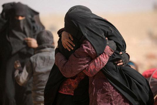 Women hug near the village of Baghouz