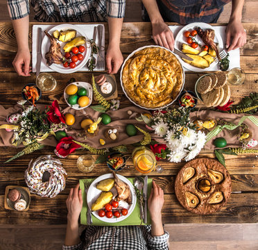 Holiday friends or family at the holiday table with rabbit meat, vegetables, pies, eggs, top view.