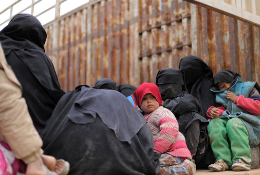 Children sit on the back of a truck near the village of Baghouz