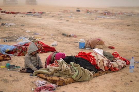 Children sit next to their injured mother near the village of Baghouz