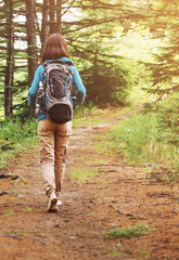 Hiker woman walking on forest path.
