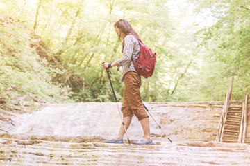 Hiker woman crossing a river with trekking poles.