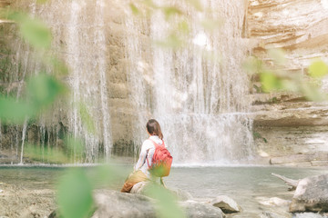 Woman resting in front of waterfall.