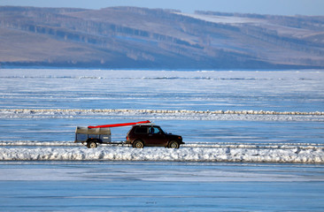 A car drives along a road connecting the banks of the ice-covered Yenisei River south of Krasnoyarsk