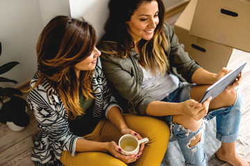 Lesbian couple looking at digital tablet