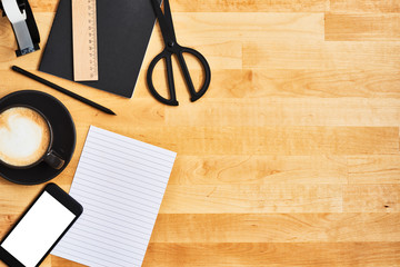 Black office or school supplies. Smartphone, notepad, pencil, scissors, scotch tape and cup of coffee on yellow wooden table. Top view. Copy space for text.