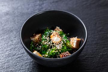 Closeup of seaweed salad with tofu seasoned with unagi sauce