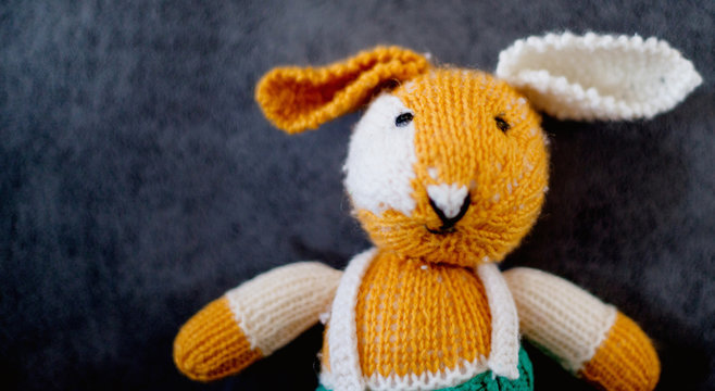Knitted toy rabbit on grey background