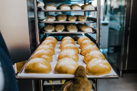 .Working woman using the bakery oven to bake the doug of the day. Bakery concept. Lifestyle..