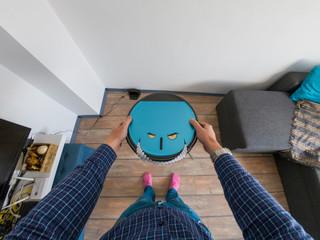 Evil robots concept. Man holding a robot vacuum cleaner