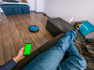 Person relaxing on a sofa with robot vacuum smart application control