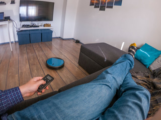 Person relaxing on a sofa with robot vacuum remote in hand