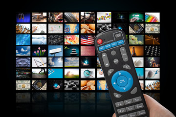 TV set with lot of pictures and hands of man with remote control.