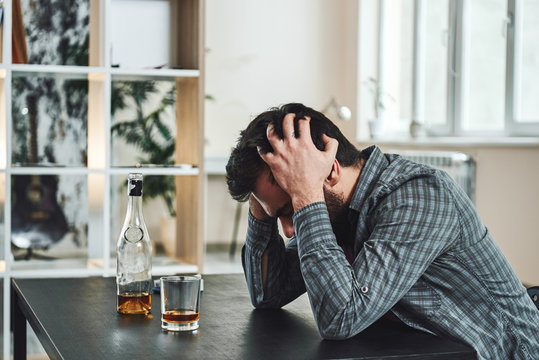 The most common way people give up their power is by thinking they don't have any. Drunk man with glass and bottle of whiskey sitting at table in kitchen. Drinking alone. Male alcoholism concept
