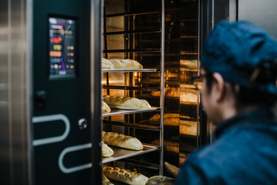 .Working woman using the bakery oven to bake the bread of the day. Bakery concept. Lifestyle..