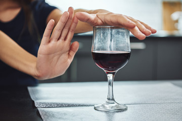 A small step toward recovery is giant progress. Addicted woman refuses to drink a glass of red wine. Close up