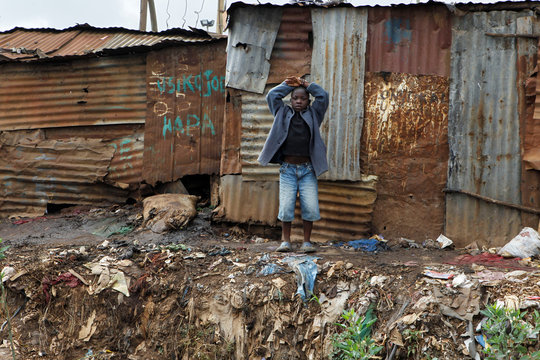A child stands behind pit latrines made of rusted iron sheets in Kibera slum within Nairobi