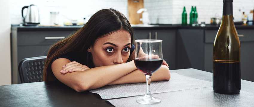 Recovery is not for people who need it, it's for people who want it. Drunk girl looking at bottle of alcohol. Soccial issue alcoholism.