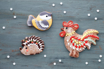 Decorated gingerbreads in shapes of rooster, tit, hedgehog and hearts on grey
