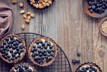 Top view on wholegrain blueberry tarts with vanilla cream on rustic wood
