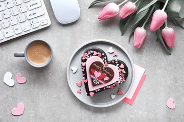 """Valentine heart cake with text """"Happy Valentine"""". Top view on working table with keyboard, mouse, cards and tulips"""
