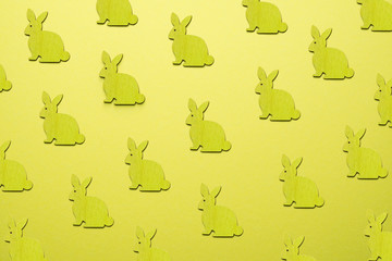 Wooden Easter Bunnies as attribute of Easter celebration. Yellow background.