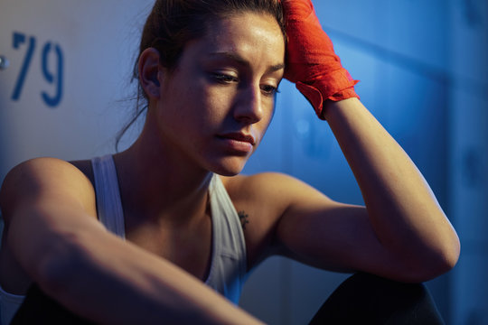 Pensive athletic woman resting in locker room after sports training.