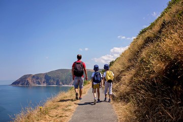 Father and two boys, family walking on a small path along the stunning Devonshire coastline near Lynmouth in Devon