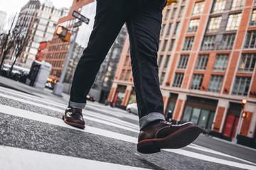 Closeup view of man legs wearing shoes crosswalk road