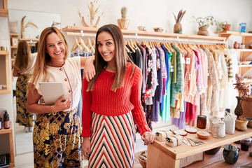 Portrait Of Two Female Sales Assistants With Digital Tablet Working In Clothing And Gift Store Wall mural