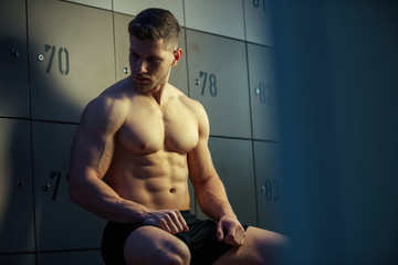 Shirtless athlete sitting in locker room before workout.