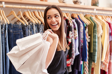 Female Customer Standing By Racks Of Clothes In Independent Fashion Store Holding Bags Wall mural