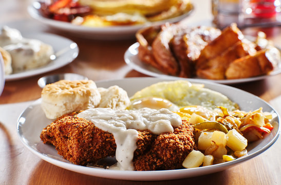 country fried steak with sunny side up eggs and biscuits