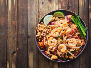 shrimp pad thai on plate in flat lay composition with copy space atop rustic wooden table