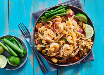 shrimp pad thai on plate in flat lay composition with copy space atop of colorful wooden table