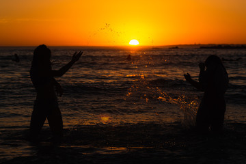 Girls splash in ocean at sunset