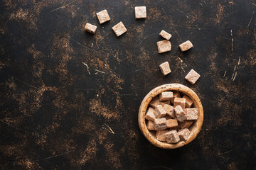 Brown sugar cubes in a bowl on a dark background. Top view, space for your text.