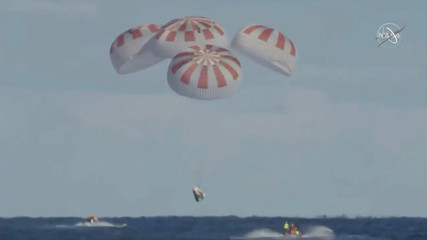 An unmanned capsule of the SpaceX Crew Dragon spacecraft descends down into the Atlantic Ocean