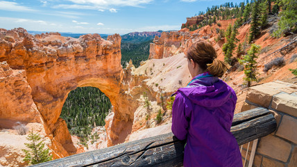 Young woman is looking at the Natural bridge rock formation in Bryce Canyon National Park, Utah, USA. Travel and adventure concept.