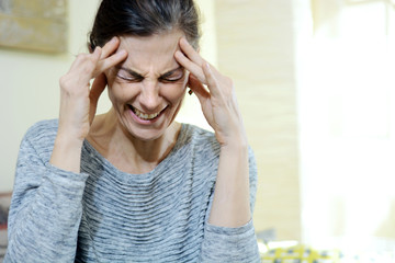 Woman has severe headache or migraine and is holding her head