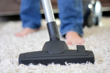 Woman makes household and cleans carpet with a vacuum cleaner